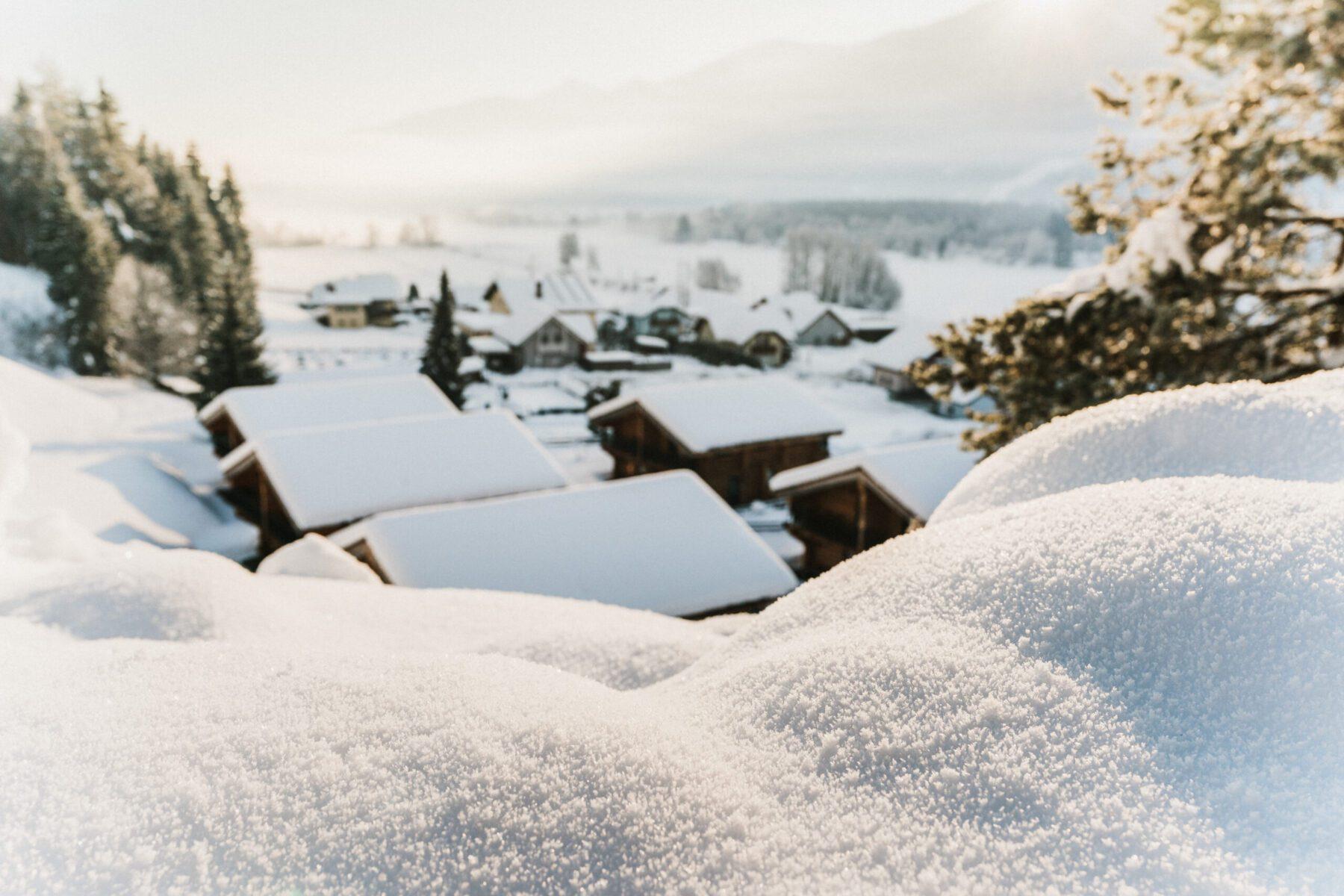 uitzicht over chalets in een dal die onder een ik pak sneeuw zitten