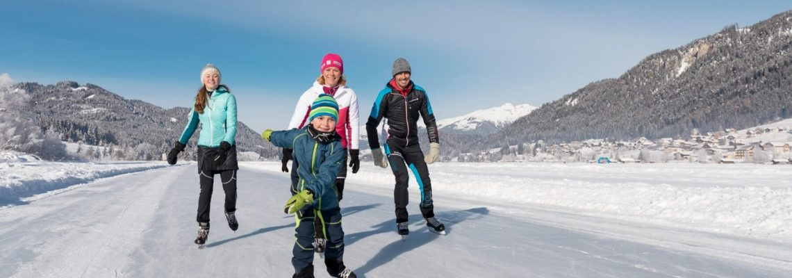 een gezin wat aan het schaatsen is op een bevroren meer met bergen op de achtergrond