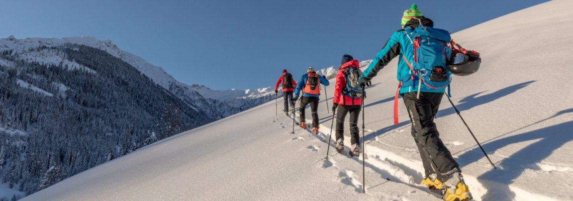 Een groep mensen die aan het langlaufen zijn op een bergrug bedekt met sneeuw