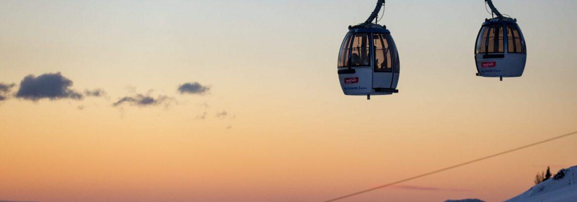 twee gondels van een skilift met op de achtergrond een uitzicht over de bergen tijdens zonsopkomst